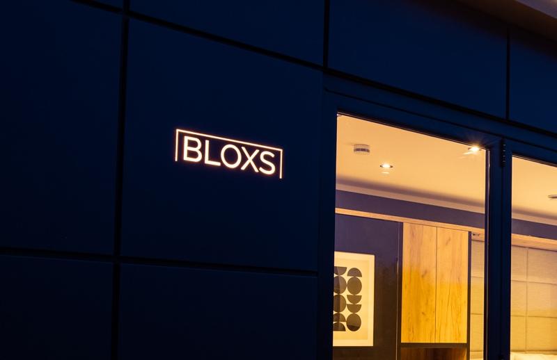 Tiny House BLOXS mit beleuchtetem Logo in der Fassade